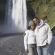 图库照片: Couple in winter clothes hugging in front of waterfall