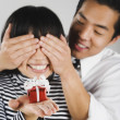 Royalty-Free Stock Photo: Asian man surprising girlfriend with gift