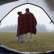 Indian couple wrapped in blanket at campsite - Stock Photo