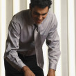 Hispanic businessman using speakerphone on conference table — Stock Photo