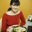Stock Photo: Businesswoman eating salad at desk
