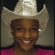 Young woman smiling for the camera in glittering cowboy hat - Stockfoto