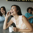 Women talking on cell phones in cafe — Stock Photo
