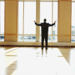 Stock Photo: Businessmstanding in sunlit room with arms outstretched