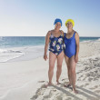 Two senior women in bathing suits smiling on beach — Stock Photo