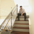 Businessman sitting at the top of a staircase - Stock Photo