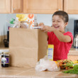 Hispanic girl unpacking groceries in kitchen - Stock Photo