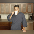 Young man drinking coffee in his kitchen — Stock Photo