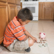 Hispanic boy counting money on floor - Stock Photo