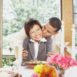 Couple kissing at the dinner table - Stock Photo