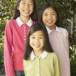 Three young Asian sisters smiling outdoors - Stock Photo
