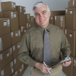 Businessman in warehouse with clipboard — Stock Photo