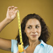 Stock Photo: Womlooking sideways holding tape measure