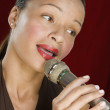 Stock Photo: Woman singing into microphone