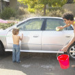 Parents with young son washing car — Stock Photo #13222352