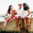 Stock Photo: Young man and women relaxing near shore