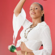 Studio shot of a female Dominican teenager with maracas — Stockfoto