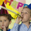 Portrait of two boys blowing noise makers at birthday party — Stock Photo