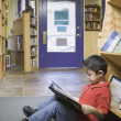 Young boy reading book at bookstore — Stock Photo #13222412