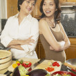 Foto Stock: Asimother and grown daughter preparing dinner