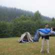 Indian man carrying girlfriends at campsite — Stock Photo #13222444