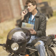 Man sitting on motorcycle using cell phone - Stock Photo