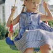 Young girl on swing in yard — Stock Photo #13222474