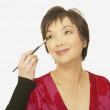 Studio shot of middle-aged Asian woman having make up put on — Stock Photo