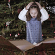 Hispanic girl opening Christmas gift — Stock Photo