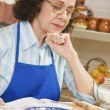 Stock Photo: Senior Hispanic woman reading cook book
