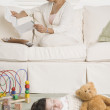 Hispanic mother reading mail while baby sleeps — Stockfoto