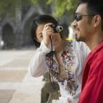 Asian woman talking photograph of Asian man outdoors — Stock Photo