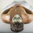 Man laying on spa table with facial treatment — Stock Photo