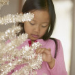 Young Asian girl looking at Christmas tree — Stock Photo