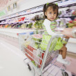 Hispanic girl in shopping cart — Stock Photo #13222627
