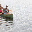 African couple paddling canoe — Stock Photo #13222630