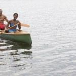 African couple paddling canoe — Stock Photo