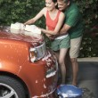 Hispanic couple washing car in driveway — Stock Photo #13222670