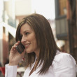 Hispanic woman using cell phone in urban scene — Stock Photo