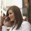 Hispanic woman using cell phone in urban scene — Stock Photo #13222673