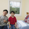 Portrait of brothers sitting on bed — Stock Photo