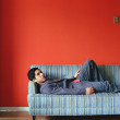 Young man lying down on couch - Stok fotoğraf