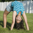 Hispanic girl doing back bend on grass — Stock Photo
