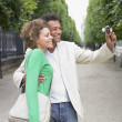 African couple taking own photograph in park — Stock Photo