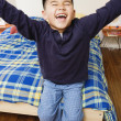 Boy sitting on bed and laughing — Stock Photo