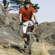 Stock Photo: Male cyclist in rugged terrain