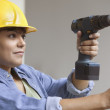 Stock Photo: Womconstruction worker with power drill and level