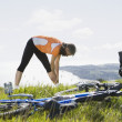 Woman stretching in grass next to bicycle — Stock Photo