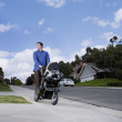 Hispanic man pushing baby stroller — Stock Photo