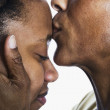 Close up of mother kissing daughter's forehead — Stock Photo